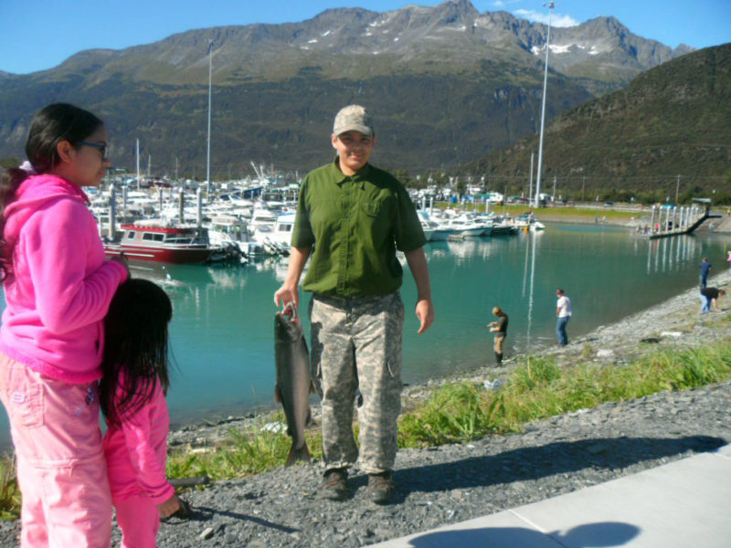 Sam Long shows off his first catch during a yearly family silver salmon fishing trip